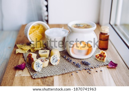 Using homemade mini wax melts in aromatherapy lamp diffuser at home interior concept. Melts making ingredients on table for unbleached beeswax, solid coconut oil, essential oil, dried flowers.