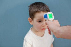 using infrared thermometer to measure child's body temperature on a blue background