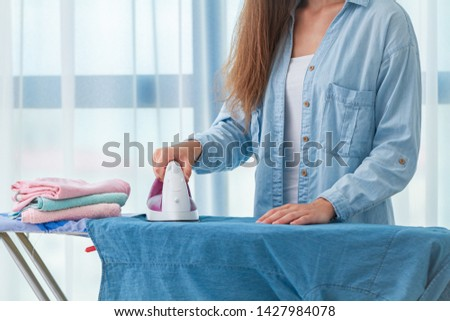 Using iron for ironing clothes after laundry at home  #1427984078