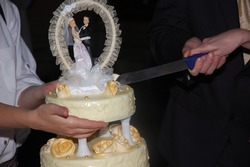 Using long knive to cut a wedding cake during a wedding reception with golden roses made of sugar.