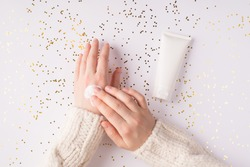 Using moisturizing cream on winter season concept.  Top flatlay overhead above close up view photo of female girl hands smearing white smooth cream on shiny background