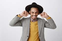 Using natural earplugs not to hear spoilers. Good-looking happy dark-skinned guy in classy hat and stylish outfit smiling with closed eyes, holding index fingers in ears, waiting for surprise