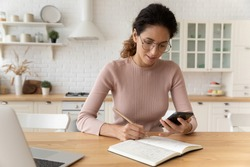 Using online open sources. Confident latina woman handwrite to notepad compare data with information at web pages. Young lady manage organize business schedule take notes from cellphone screen by hand