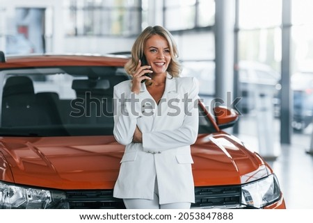 Using phone. Woman in formal clothes is indoors in the autosalon.
