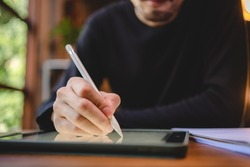 using professional digital tablet technology to write a business work, modern online screen cyberspace communication, hand writing via white pen, lifestyle same laptop computer or notebook using