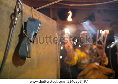 Using safety gas testing detector atmosphere while blurry pic of rope access welder wearing fully safety uniform fall protection helmet, welding glove harness, commencing welding, in confined space