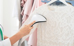Using steaming iron to ironing dress in laundry room. Doing stream vapor iron for press clothes in hand. Showroom or atelier
