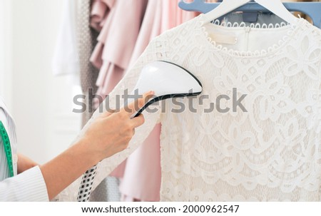 Using steaming iron to ironing dress in laundry room. Doing stream vapor iron for press clothes in hand. Showroom or atelier Stockfoto ©