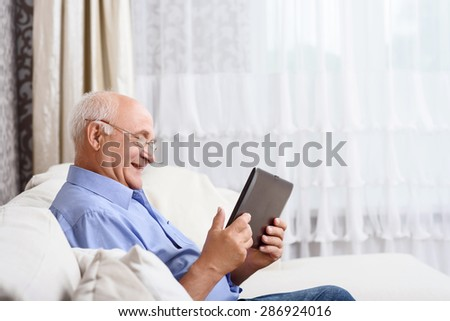 Using technologies. Portrait of old man sitting on couch and using tablet.