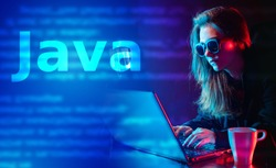 Using the Java programming language. The concept of web development. Programming in JAVA. A girl with dark glasses works as a programmer.