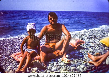USSR, ABKHAZIA, BLACK SEA - CIRCA 1980: Vintage photo of father with little son on Black sea beach in Abkhazia, USSR