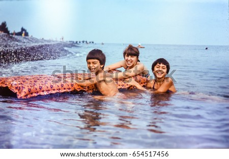 USSR, ABKHAZIA, LESELIDZE - CIRCA 1981: Vintage photo of mother with children laughing in Black sea water at beach landscape in Abkhazia, USSR