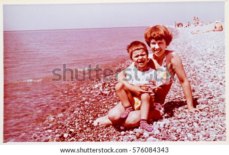 USSR, ABKHAZIA, LESELIDZE - CIRCA 1979: Vintage photo of mother with little son on Black Sea beach
