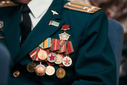 USSR and Russia veteran soldier medals of war in Afghanistan and WWII. Close up World War veteran military service ribbons and medals of honor on green colonel jacket. Victory Day celebration.