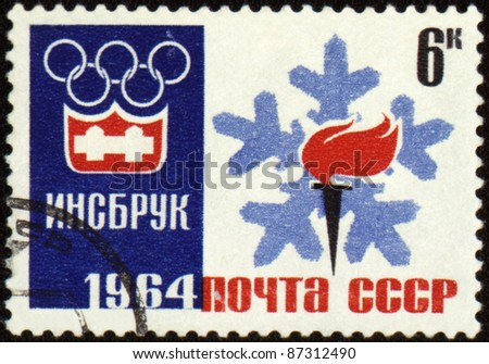 USSR - CIRCA 1964: A post stamp printed in USSR shows Olympic emblem and torch with flame, devoted to the Olympic Winter Games in Innsbruck, series, circa 1964