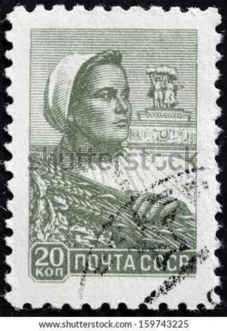 USSR - CIRCA 1958: A stamp printed by USSR (Russia) shows a woman farm worker holding a wheat bundle, circa 1958.