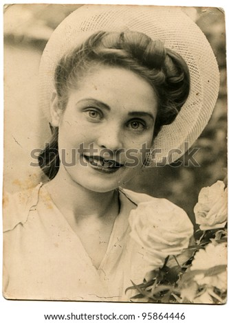 USSR - CIRCA 1947: Portrait of a young beautiful woman with white roses, circa 1947