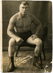 USSR - CIRCA 1930s: Studio portrait of a fighter, sitting on a chair, circa 1930s, Russian text - T Bunin