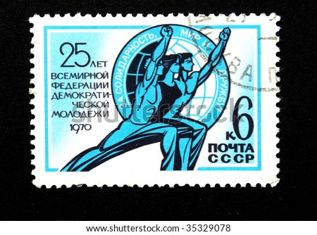 USSR - CIRCA 1970: stamp printed in the USSR devoted  25 anniversary of The world organization of democratic youth shows stylized image of two young men and girls on background of globe, circa 1970.