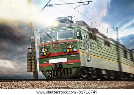 USSR electrical green train with red star going at high speed with ray of light at dramatic sky background