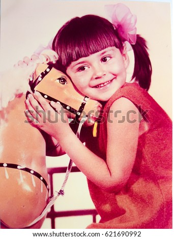 USSR, LENINGRAD - CIRCA 1974: Vintage photo of little smiling girl portrait with toy horse in Leningrad, USSR