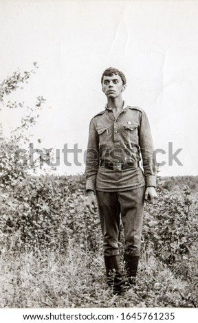 USSR, LENINGRAD - CIRCA 1968: Vintage photo of Soviet Army soldier Nikolay Tsyukevitch standing in field and looking forward