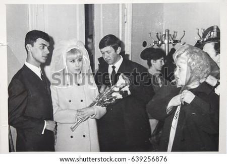 USSR, LENINGRAD - CIRCA 1969: Vintage photo of wedding couple with guests. Vintage photo of wedding couple. Just married couple. Soviet bride and groom wedding in Leningrad, USSR