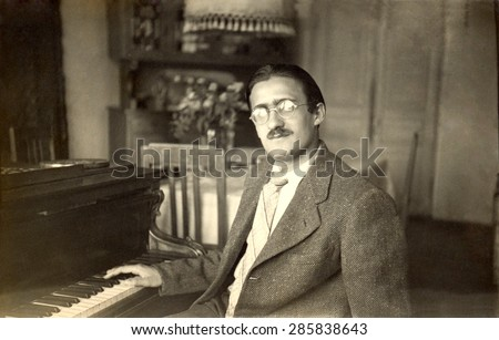 USSR, Russia, - CIRCA 1948: An antique black & white photo of a man sitting near the piano, circa 1948