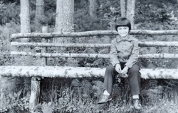 USSR, WESTERN UKRAINE - CIRCA 1982: Vintage photo of little boy Sergey Tsyukevitch sitting on wooden bench in forest in Western Ukraine, USSR