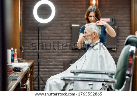 Usual day at barbershop. Young barber girl cutting hair of handsome bearded middle-aged man. Side view. Beauty salon and barbershop concept. Focus on a barber and client. Barber tools. Mens haircut