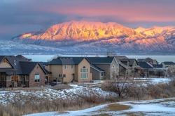 Utah Valley neighborhood on a winter scene with Wasatch Mountain lit by sunset