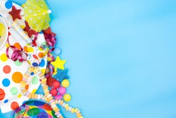Utensils for children's birthdayparties and parties such as smarties, umbrellas and mugs on a blue background. Horizontal