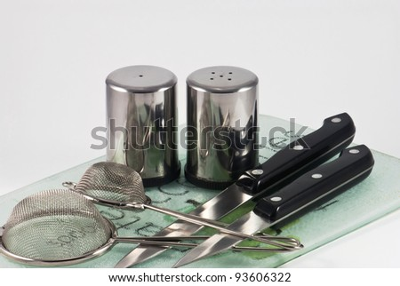 Utensils in a kitchen - knifes, salt and pepper cellars with filters