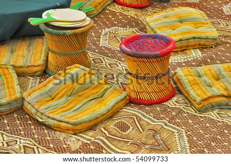 Utensils in ancient authentic bedouin tent - carpets, pillows and padded stools