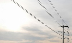 Utility pole. Electrical wires. Power lines against the sunrise sky background. Rows of poles accompanying roads.