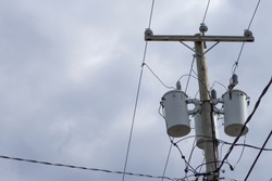 Utility pole supporting wires for electrical power distribution, coaxial cable for cable television, telephone and internet cable.