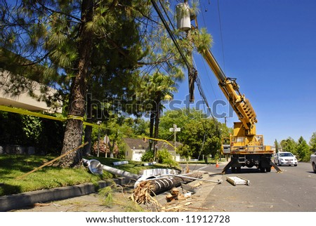 Utility truck lifts a severed power pole and lines after an accident - stock photo