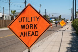 Utility Work Ahead sign on sidewalk next to street warns traffic about work project zone in distance.