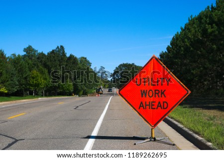Utility Work Ahead sign with service vehicle down the street #1189262695