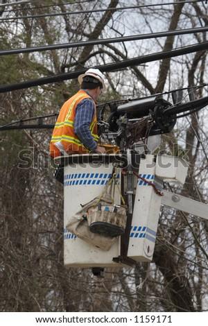Utility Worker Repairing Lines in Cherry Picker Bucket from Truck