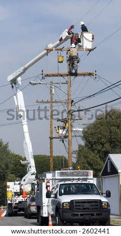 utility workers doing maintenance on power pole
