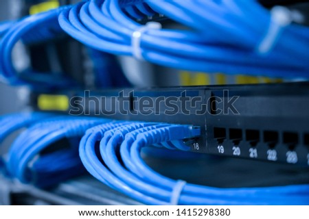UTP Cabling patch panel with blue cables connected in data center room #1415298380