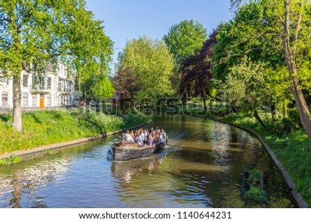 Utrecht, Netherlands - May 5, 2018:A view of the canals in Utrecht. People enjoying the nice weather while having a peaceful boat ride in the waterways of the fourth biggest city in the Netherlands.