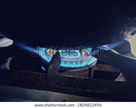 uttarakhand,india-3 june 2020:gas stove with blue flame.this is a picture of a gas stove with blue flame and cooking utensil on it.blue flame on gas stove.