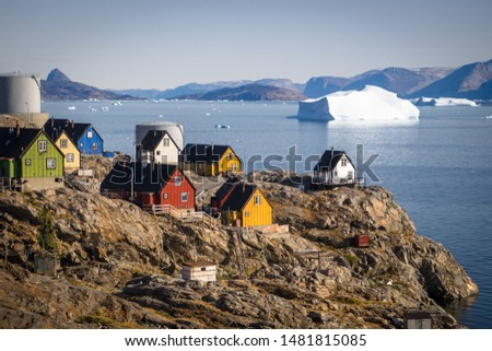Uummannaq, Greenland hill side view with several colourful houses and large icebergs.  Large mountains and glaciers in the background #1481815085