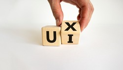 UX design or UI design. Male hand turns cube and changes word 'UX - user experience' to 'UI - user interface'. Beautiful white background. Business and UI or UI concept. Copy space.