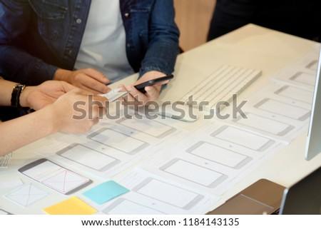ux designer team creative graphic planning application development a paper prototype smartphone layout.
