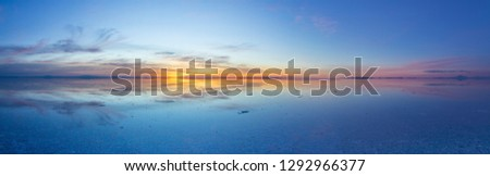 Uyuni reflections. One of the most amazing things that a photographer can see. A sunrise over infinity, the infinite horizon cover by water offer us awe colorful sky symmetric reflections on water  #1292966377