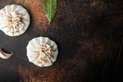 Uzbek Manti. Manti or manty dumplings, popular uzbek-asian dish set, on old dark rustic background, top view flat lay, with copy space for text
