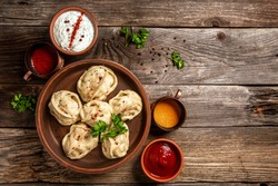 Uzbek prepared boiled Manti or manty dumplings in a traditional bowl on wooden table. banner menu recipe place for text.